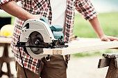 Close-up of carpenter cutting a wooden plank