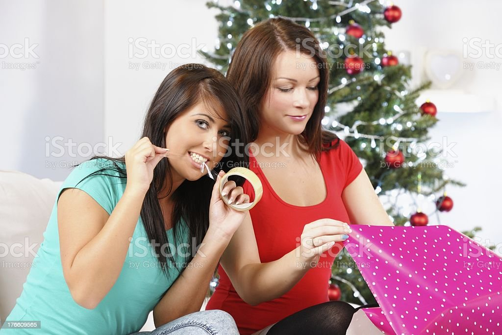 Close-up Of Caucasian Young Women Wrapping Christmas Presents stock photo