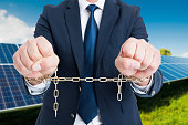Closeup of chained businessman hands