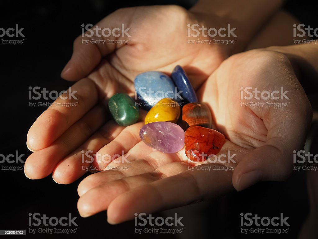 Close-up of Chakra stones in woman hand stock photo