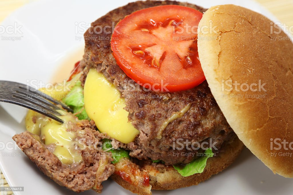 Close-up of cheeseburger with fork stock photo