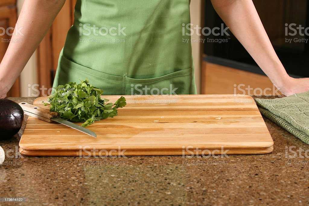 Close-up of chef behind cutting board with chopped lettuce stock photo