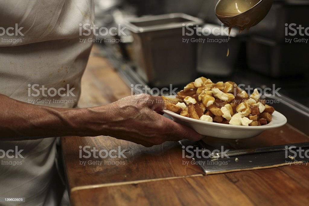 Close-up of chef hands preparing a dish of poutine stock photo