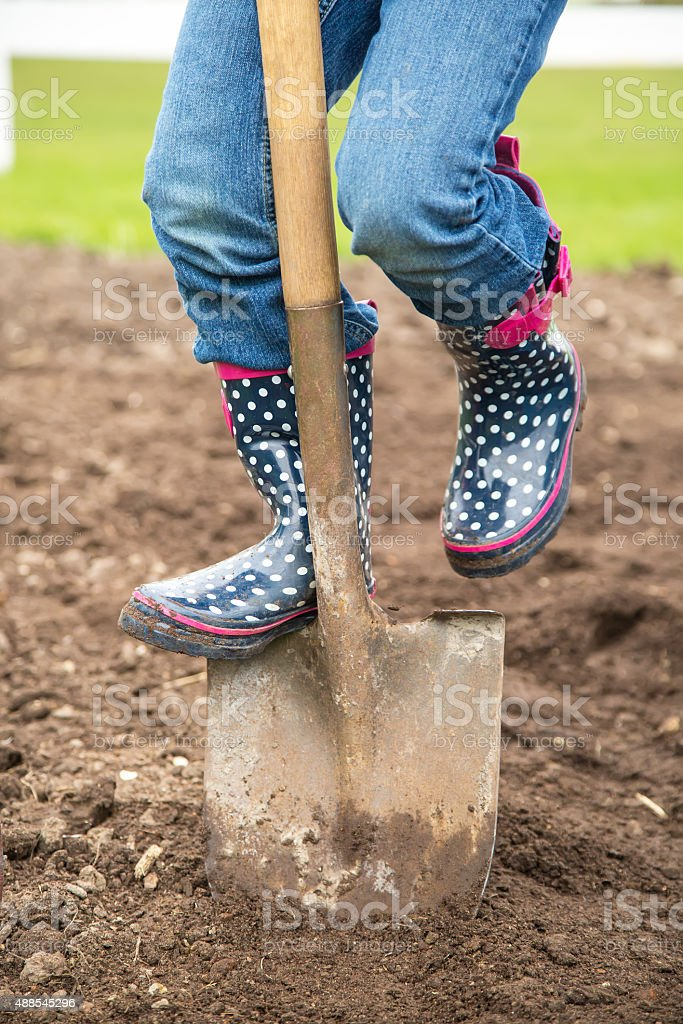 Close-Up of Child Digging Hole With Shovel In Garden stock photo