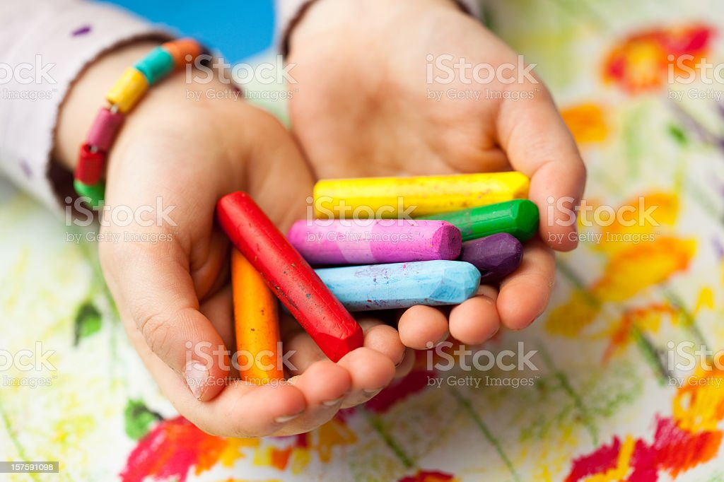Close-up of child holding colorful wax crayons in hands stock photo