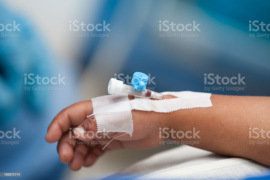 Close-up of child's hand undergoing IV blood transfusion stock photo