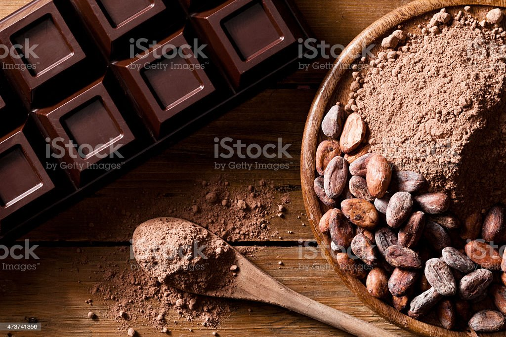 Close-up of chocolate bar, cocoa beans and ground cocoa stock photo