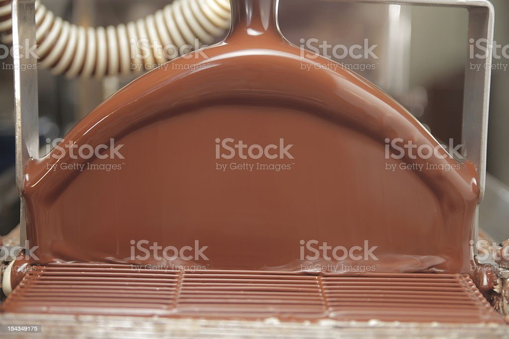 Close-up of chocolate flowing through a machine at a factory royalty-free stock photo