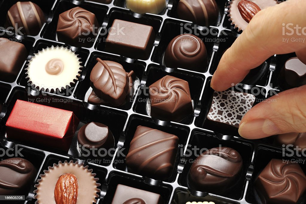 Close-up of choosing a luxury chocolate from box stock photo