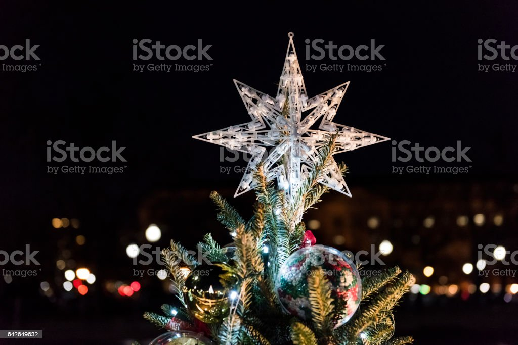 Closeup of Christmas tree star with bokeh outside at night stock photo