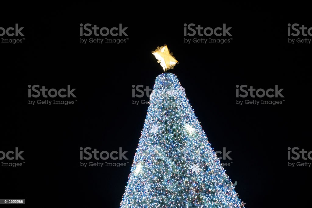 Closeup of Christmas tree star with outside at night illuminated stock photo