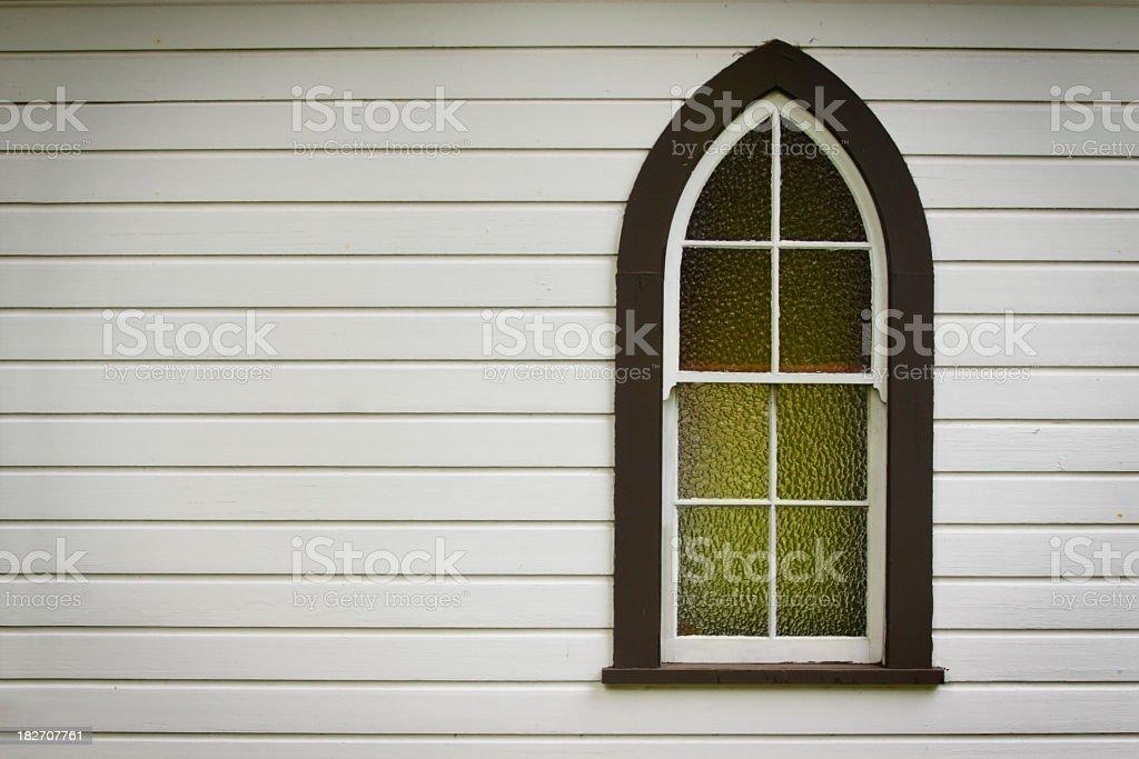 Closeup of church window with green light inside stock photo
