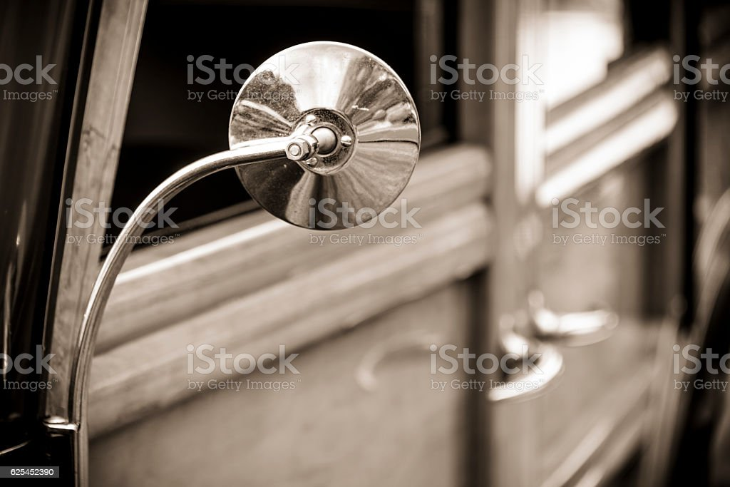 Close-up of classic car mirror with wooden side panels. stock photo