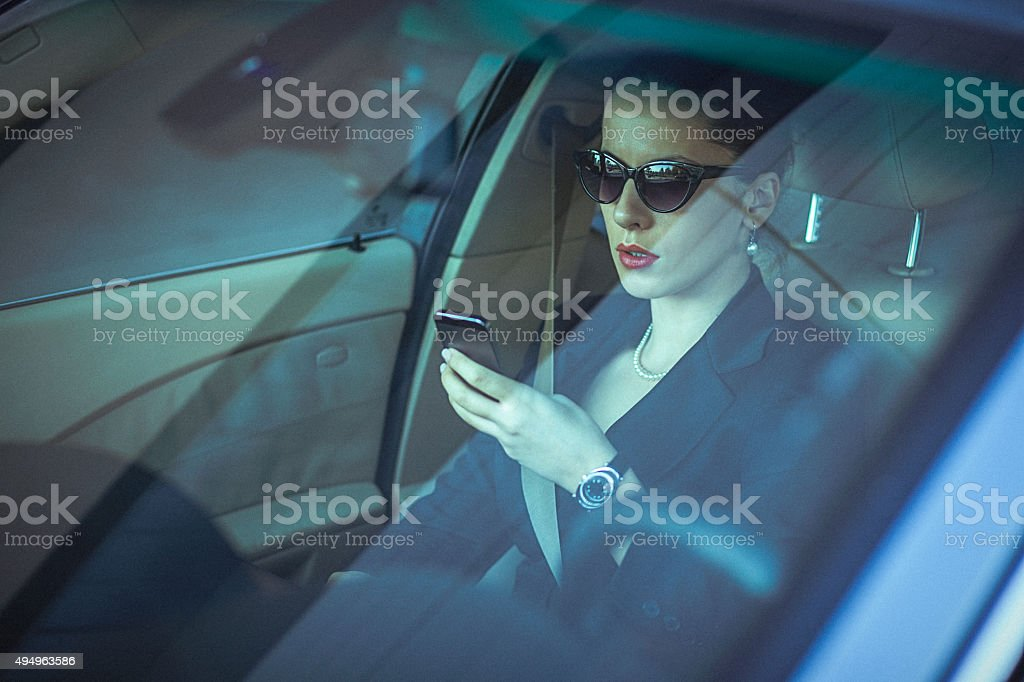 Close-up of classy woman, using mobile phone in the car stock photo