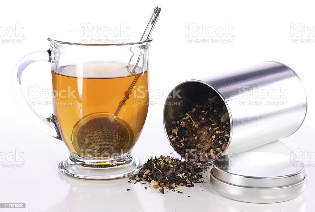 Close-up of clear herbal tea with a can of grounded herbs stock photo