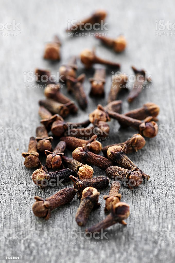 Close-up of cloves laying on a wooden surface stock photo