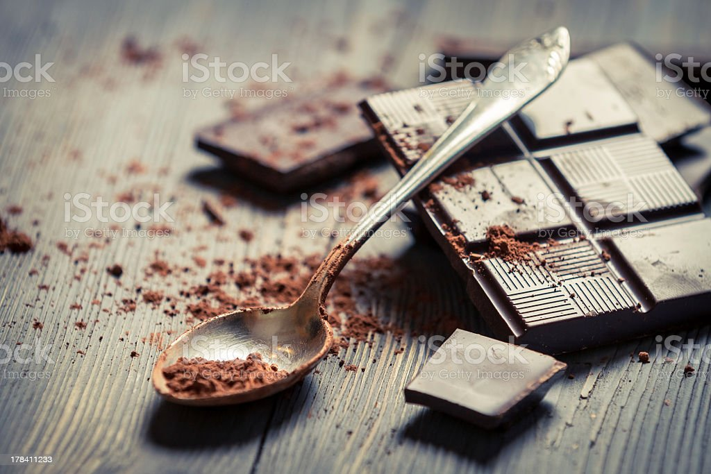 Close-up of cocoa power on spoon and dark chocolate squares stock photo