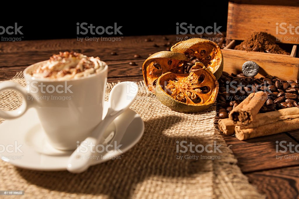 Close-up of coffee cup, dried orange fruit and cinnamon sticks stock photo