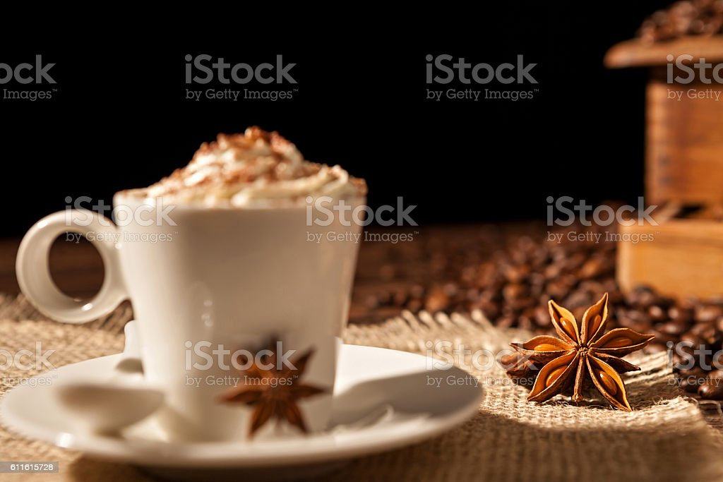 Close-up of coffee cup with whipped cream and star anise stock photo