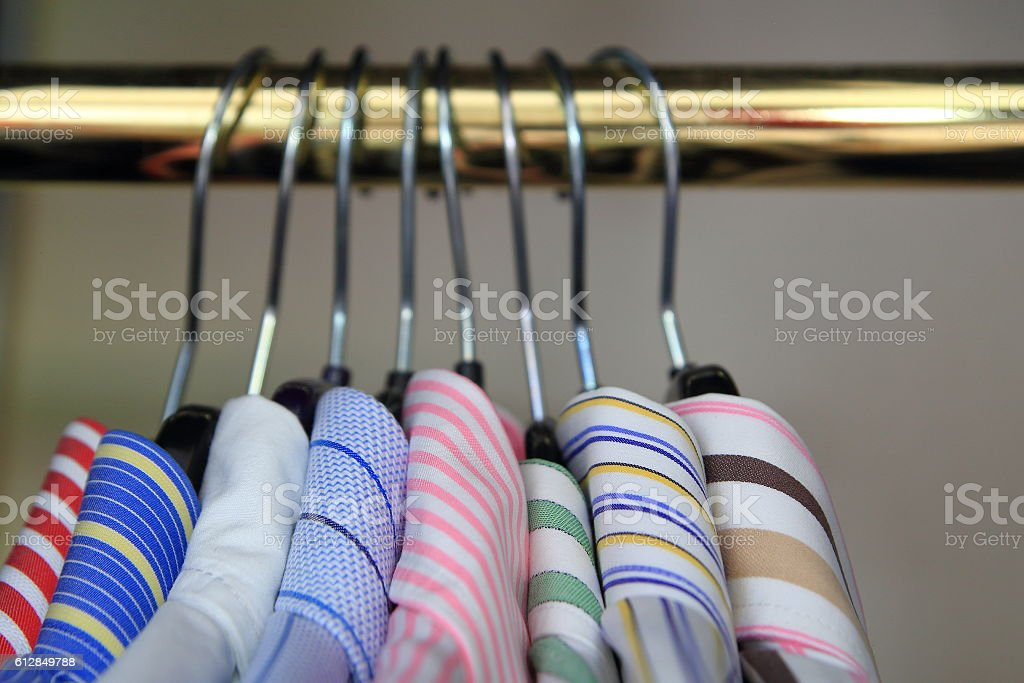 Closeup of collars of men's shirts hanging on a rail stock photo