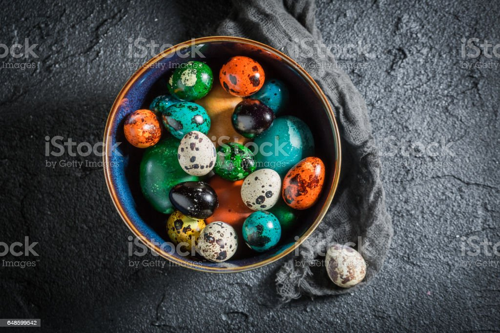 Closeup of colorful Easter eggs in blue bowl stock photo