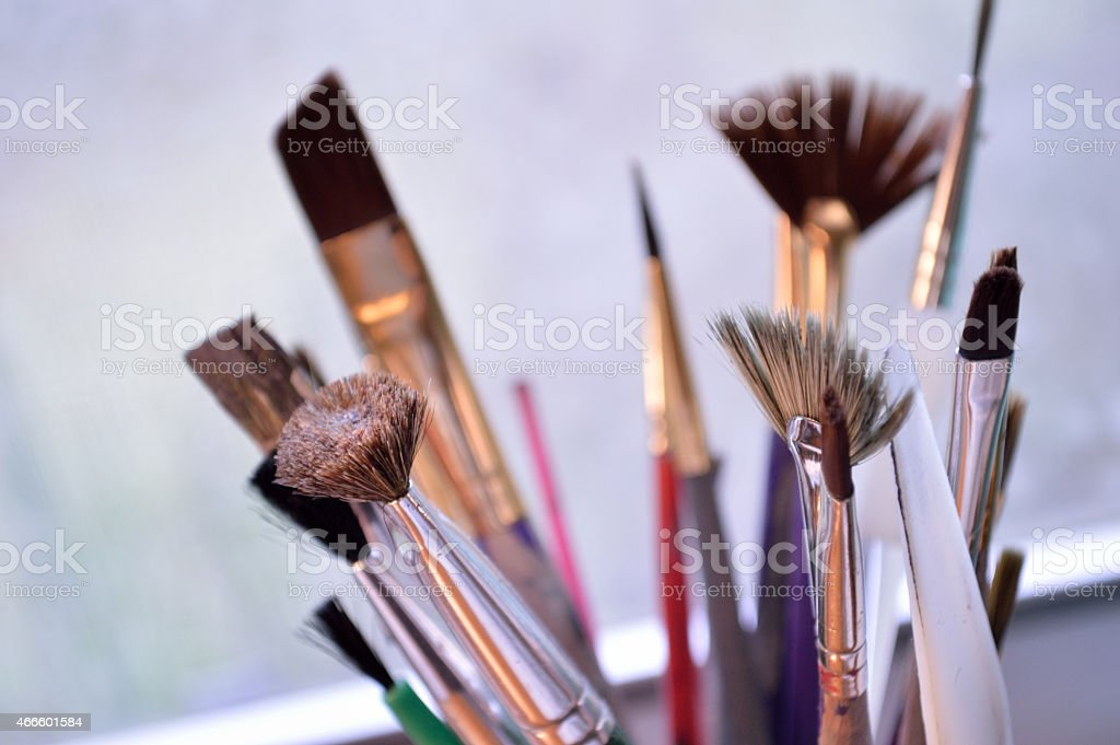 Closeup of colorful paintbrushes in an art studio stock photo
