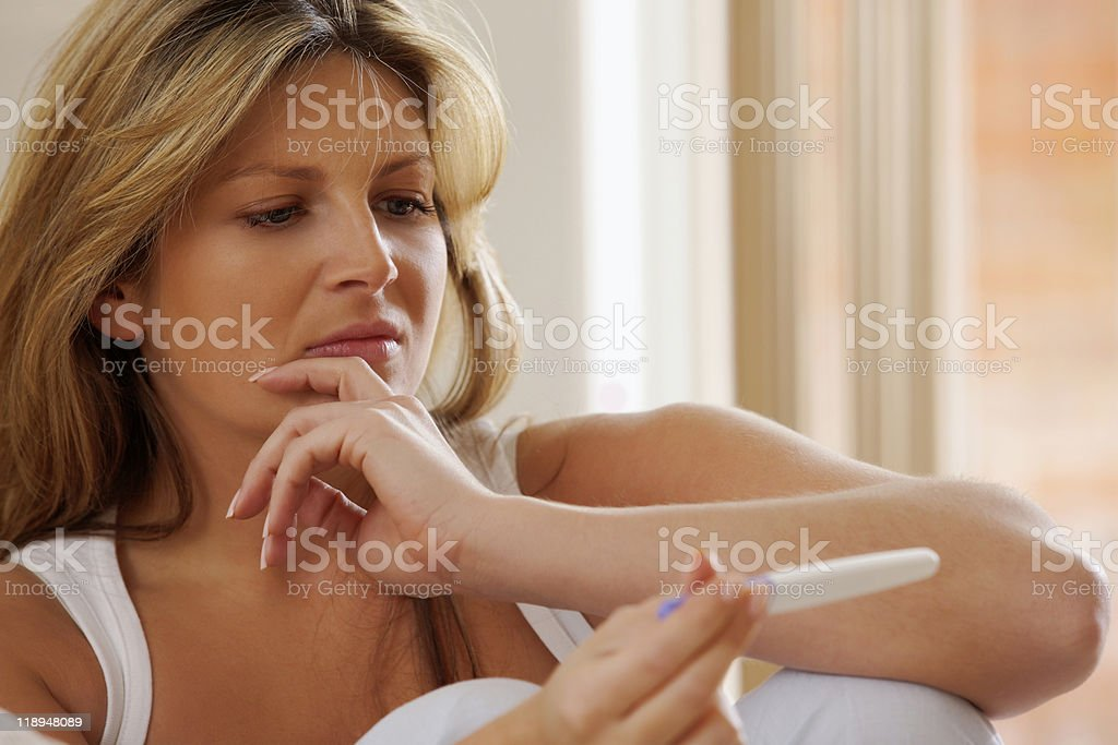Close-up of concerned woman sitting and looking at pregnancy test stock photo