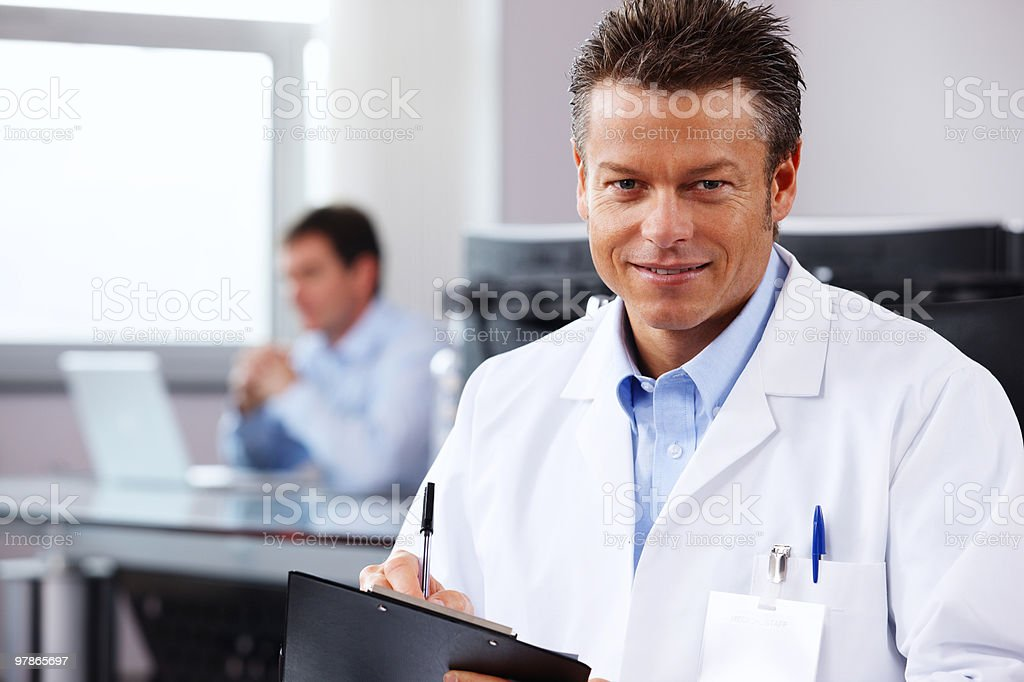 closeup of confident Doctor writing reports in modern office royalty-free stock photo