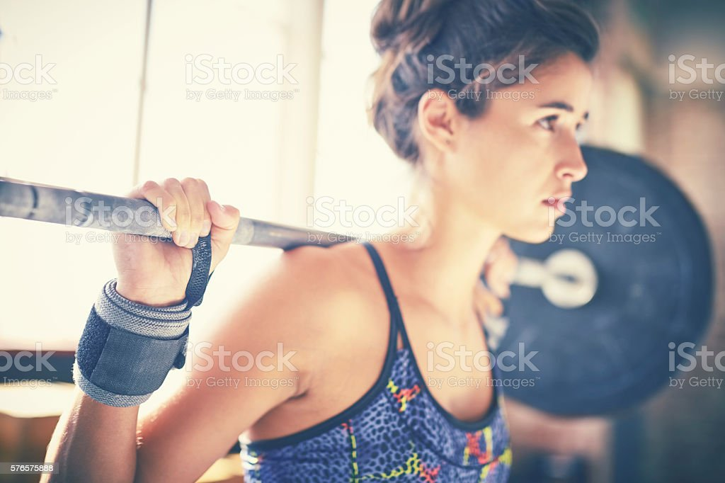 Close-up of confident woman exercising with barbell in gym stock photo