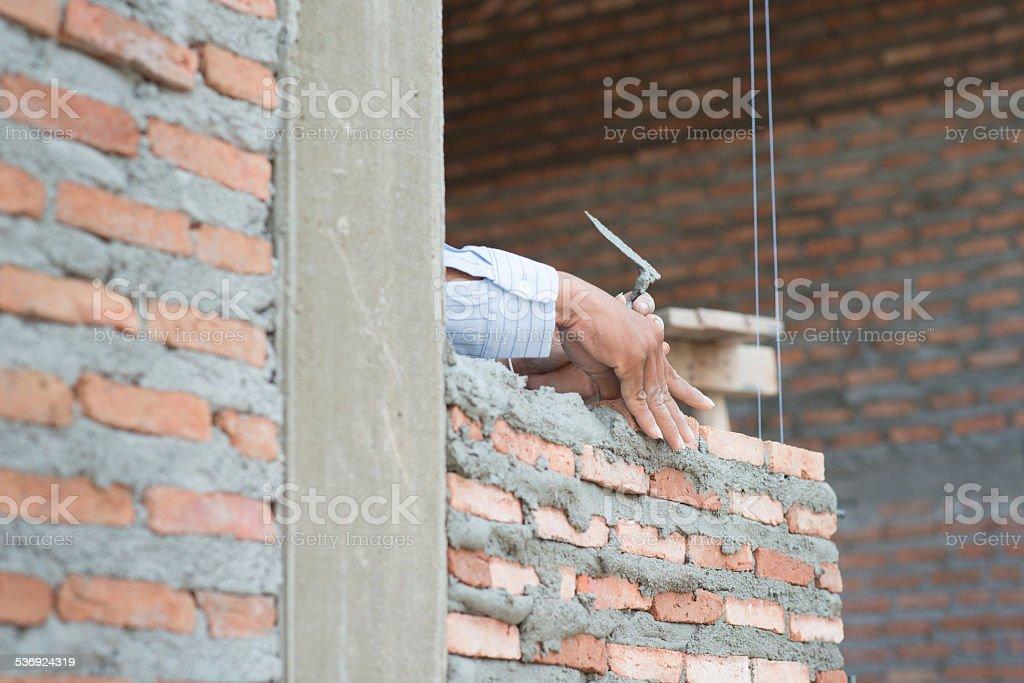 Close-up of construction process mason work with brick installat stock photo