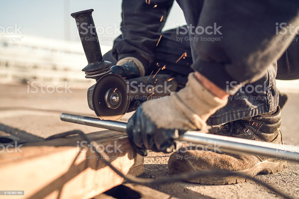 Close-up of construction worker cutting metal bar with grinder. stock photo