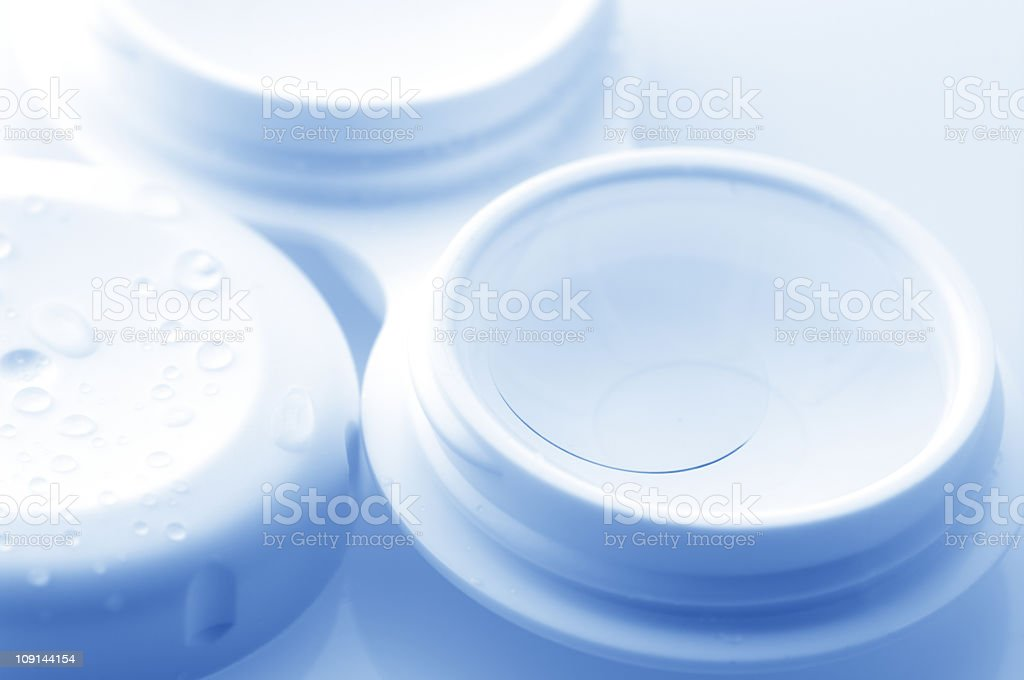 A close-up of contact lenses in a white container stock photo