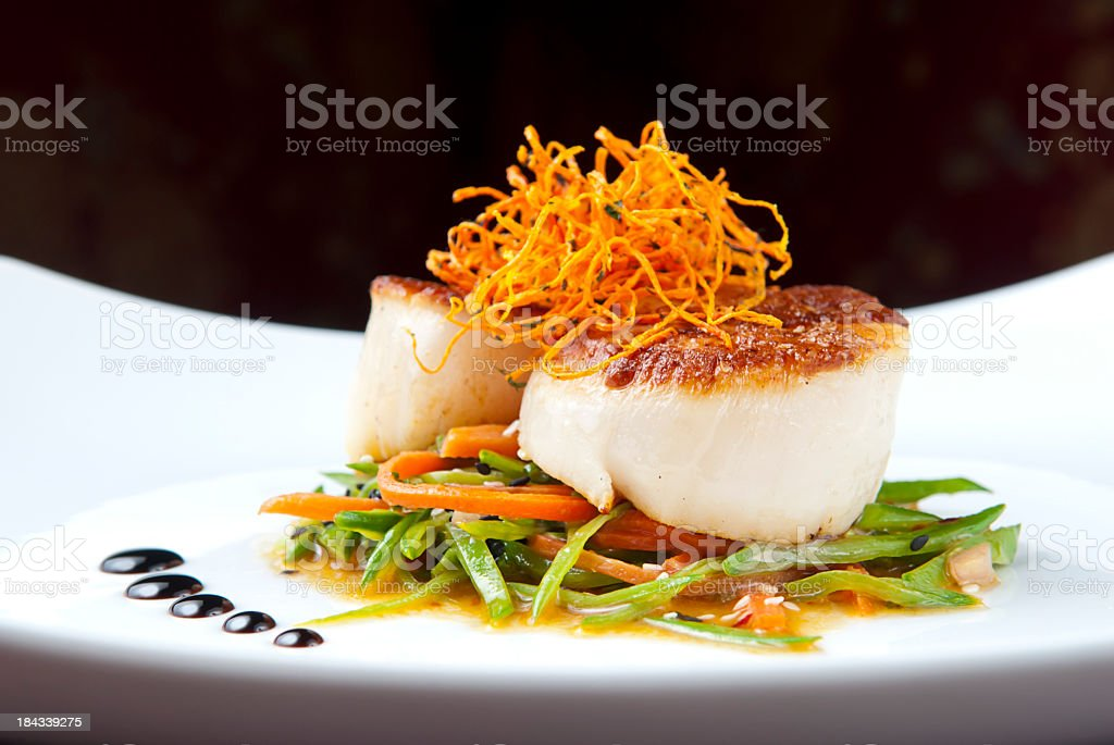 Close-up of cooked scallops on bed of vegetables stock photo