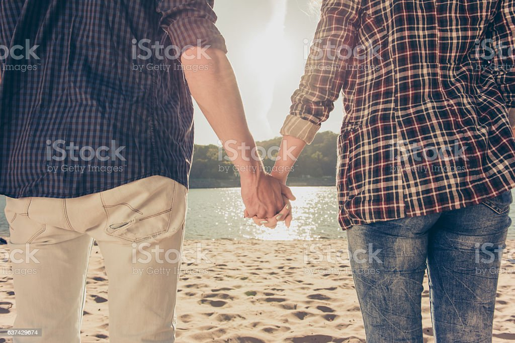 Closeup  of couple in love holding hands near the river stock photo