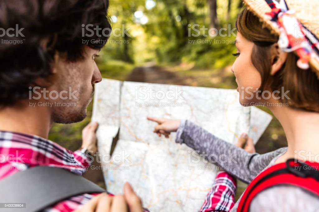 Close-up of couple looking for direction on map in nature. stock photo