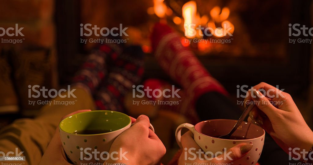 Close-up of couple with coffee cups by fireplace stock photo