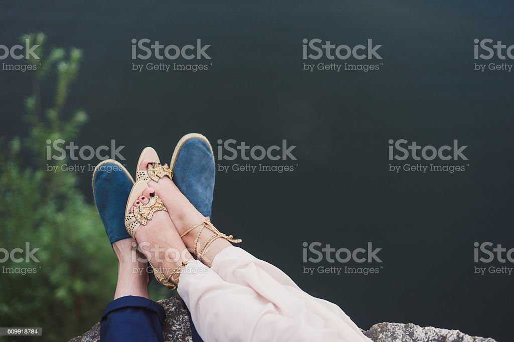closeup of couple's casual footwear on the riverside stock photo