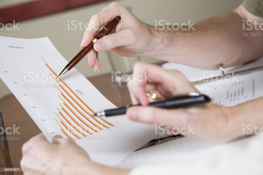 Closeup of co-worker's hands going over sales data royalty-free stock photo