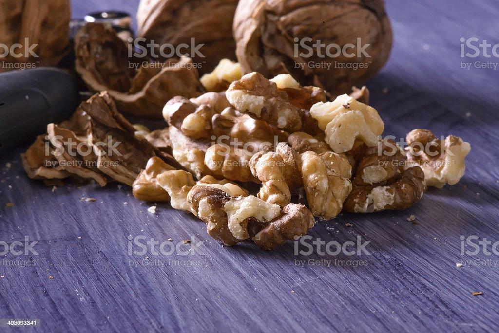 Closeup of cracked walnuts on purple table stock photo