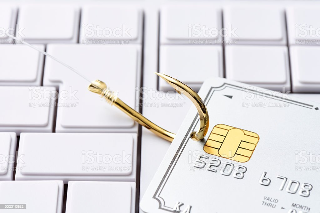 Close-up of credit card with fishing hook on computer keyboard stock photo