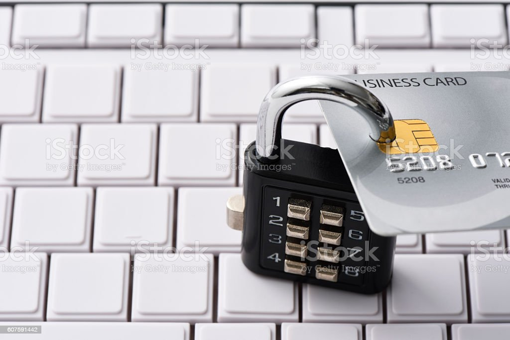 Close-up of credit card with locked padlock on computer keyboard stock photo