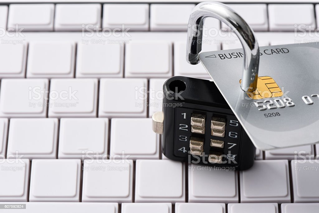 Close-up of credit card with unlocked padlock on computer keyboard stock photo