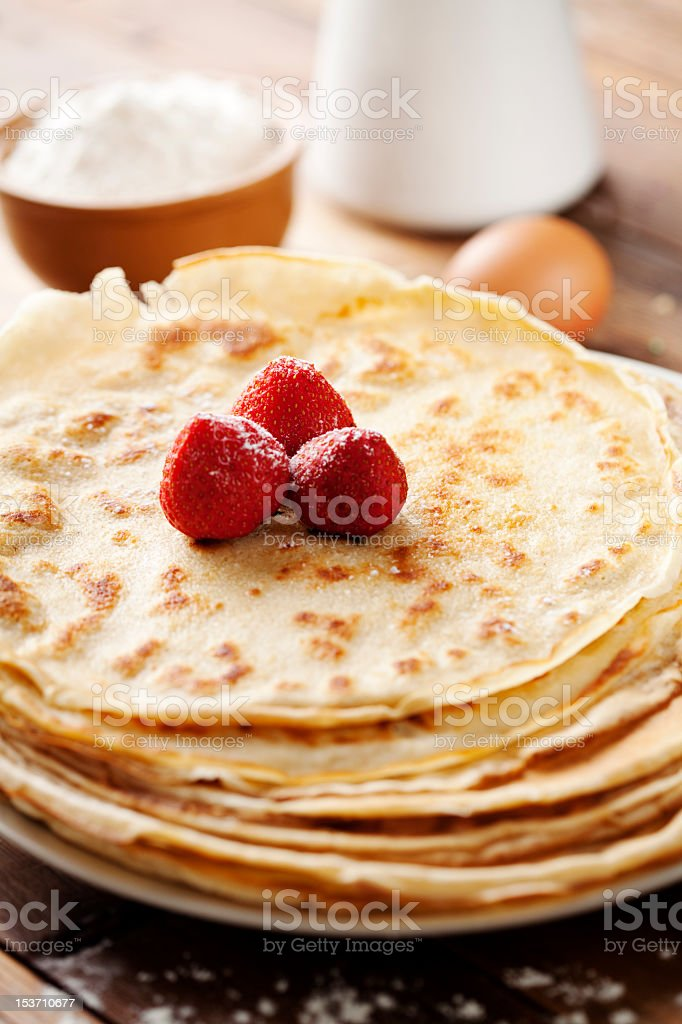 A closeup of crepes with strawberries on it stock photo