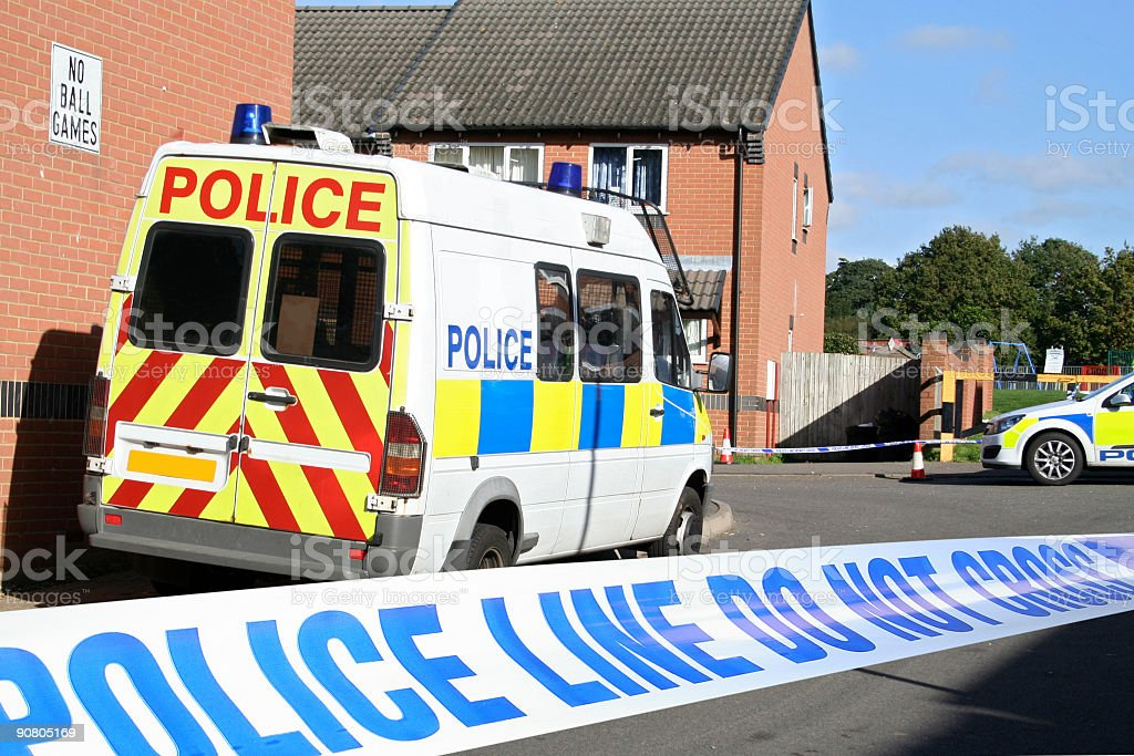 Close-up of crime scene tape with view of police van stock photo