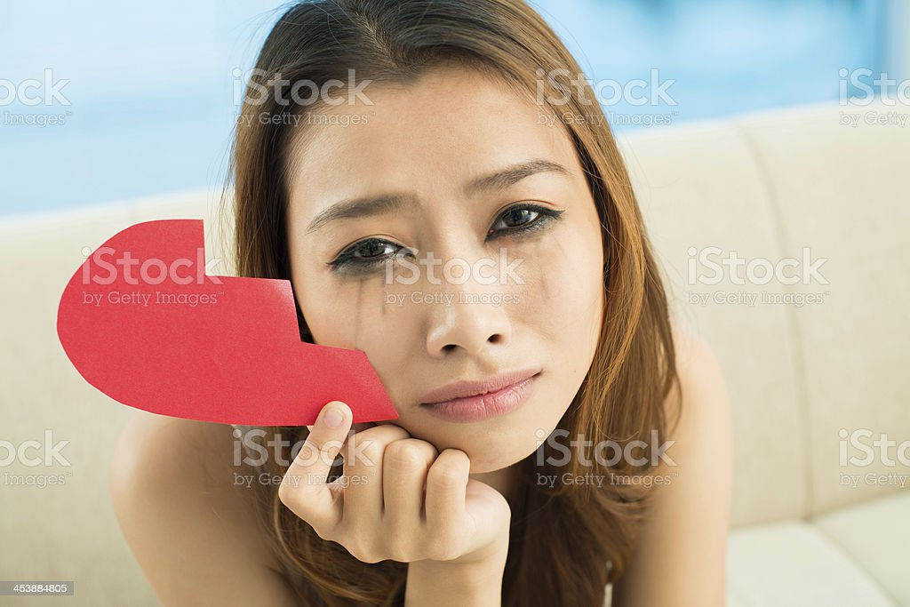 Close-up of crying girl on couch with smudge eyes stock photo
