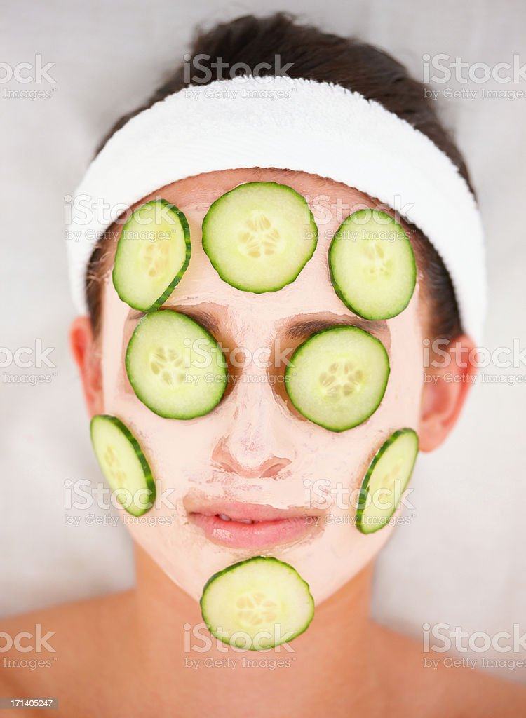 Closeup of cucumber slices and facial mask on a young girl's face stock photo