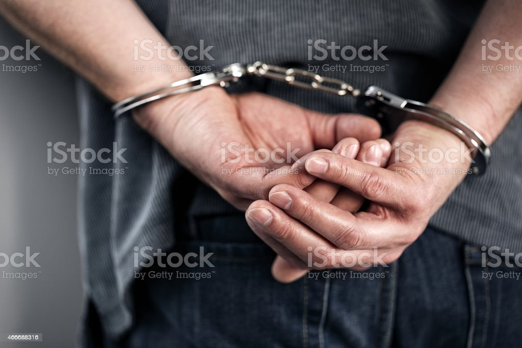 Close-up of cuffed criminal hands stock photo