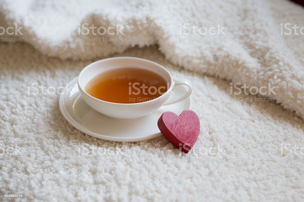 Closeup of cup of tea and red heart figure stock photo