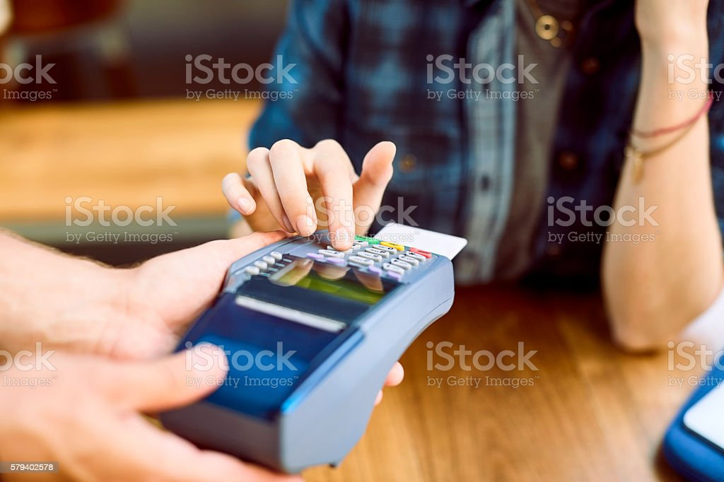 Close-up of customer entering pin on card reader stock photo
