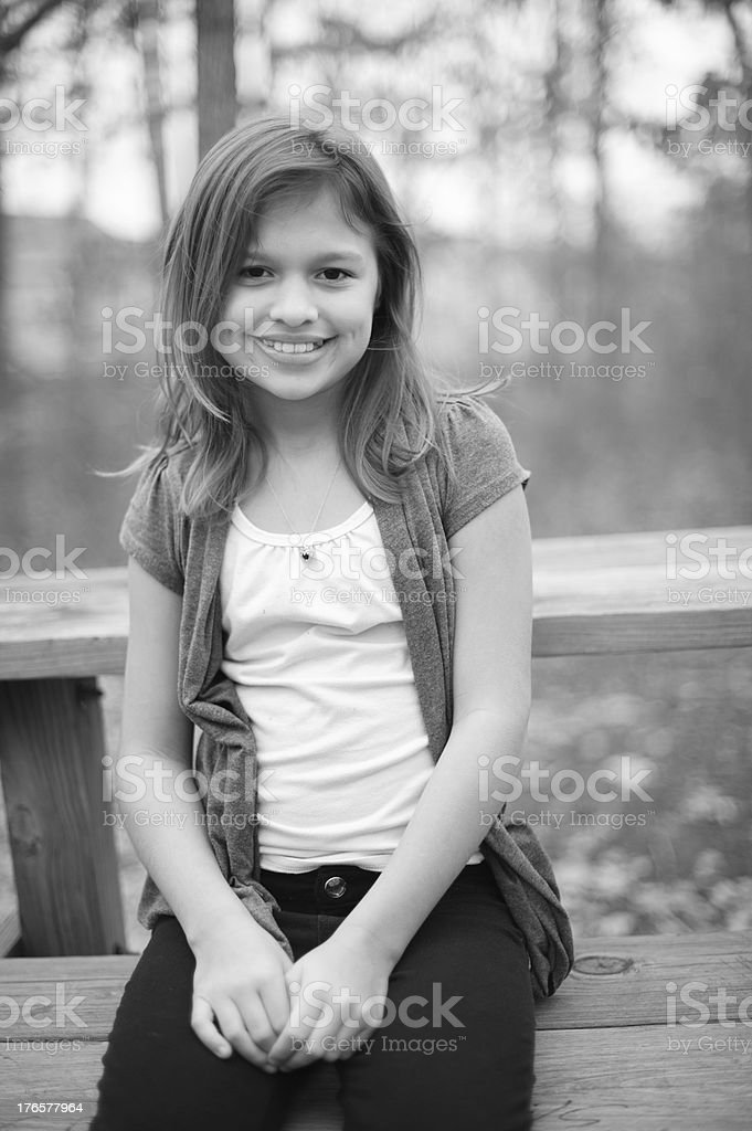 Closeup of Cute Girl With Dimples Sitting on Bench Outside royalty-free stock photo